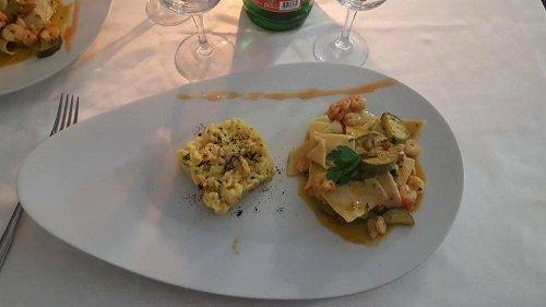 un piatto di paccheri con gamberi e zucchine e un tortino di riso