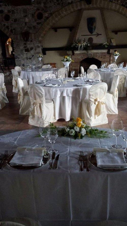 sala da pranzo di un ristorante con tavoli apparecchiati per un ricevimento