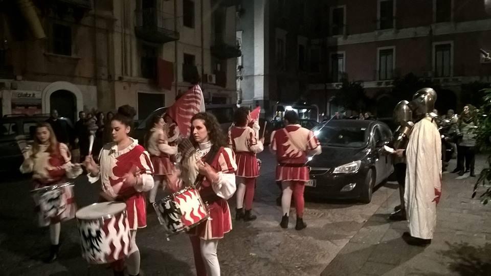 una parata di donne con dei tamburi e altre persone vestite da guerrieri
