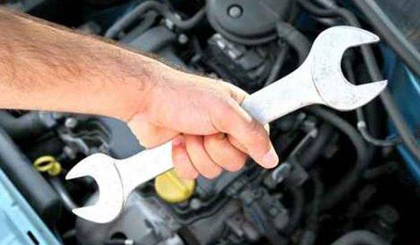 una mano che impugna una chiave inglese e dietro la zona motore di un veicolo