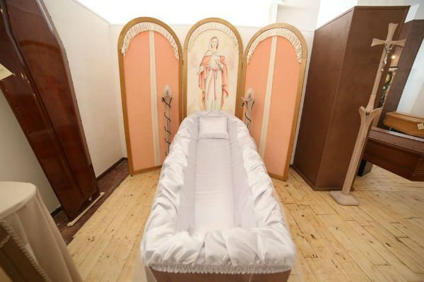 una bara con un telo bianco e un pannello di legno con l'immagine della Madonna