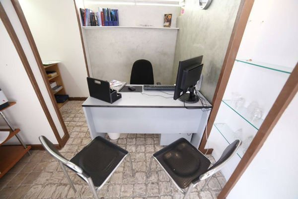 una scrivania con un computer e tre sedie