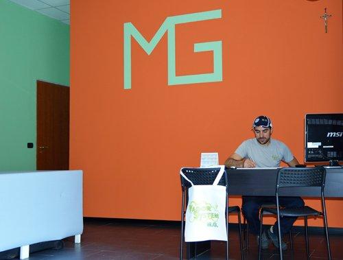 muro con scritta MG una scrivania e un addetto