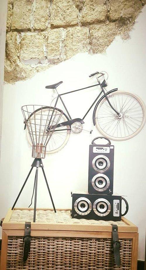 una valigetta di paglie e supra degli altoparlanti e una bicicletta appesa al muro