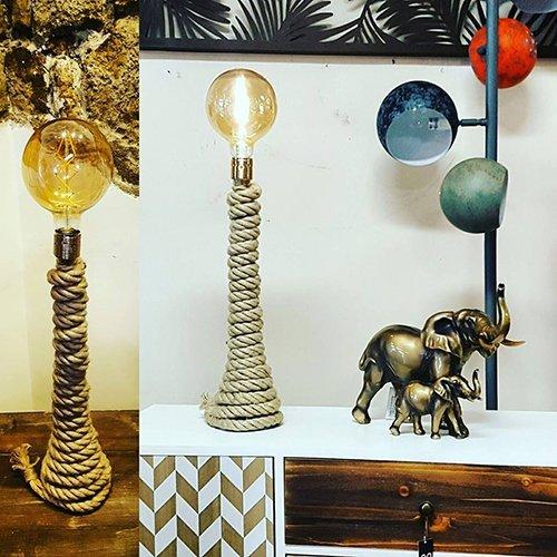 una lampada con una base di una corda arrotolata e accanto delle statuette di due  elefanti