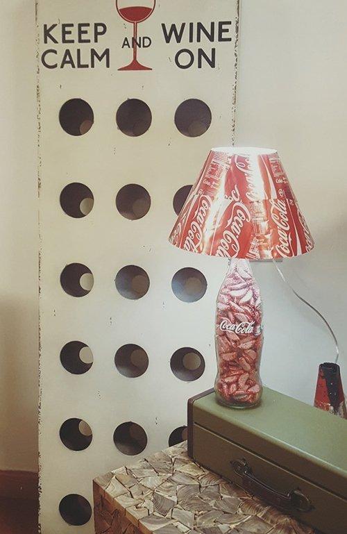 una lampada con un paralume rosso e una base di una bottiglia di Coca Cola