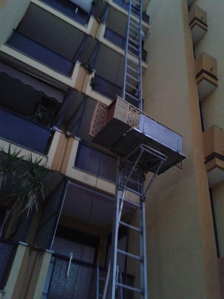 una lunga scala con una piattaforma che trasporta dei mobili