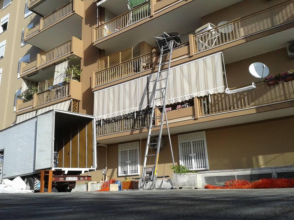 un camion con il rimorchio aperto e una scala per traslochi vicino a un condominio