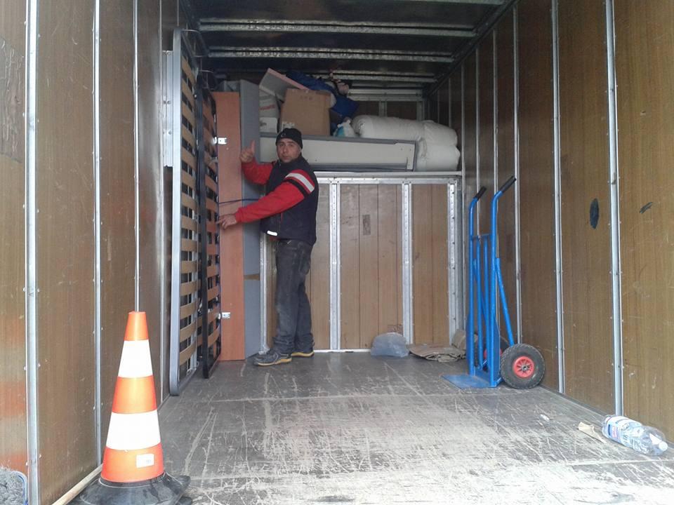 un uomo con il pollice in su dentro al rimorchio di un camion
