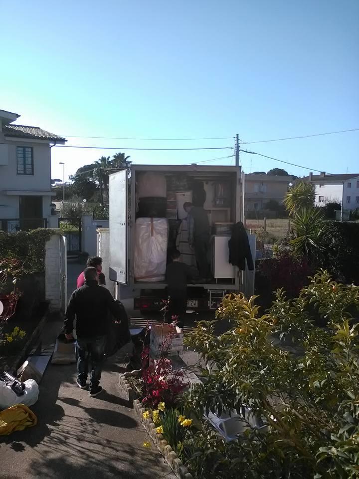 delle persone che caricano dei mobili nel camion in un giardino