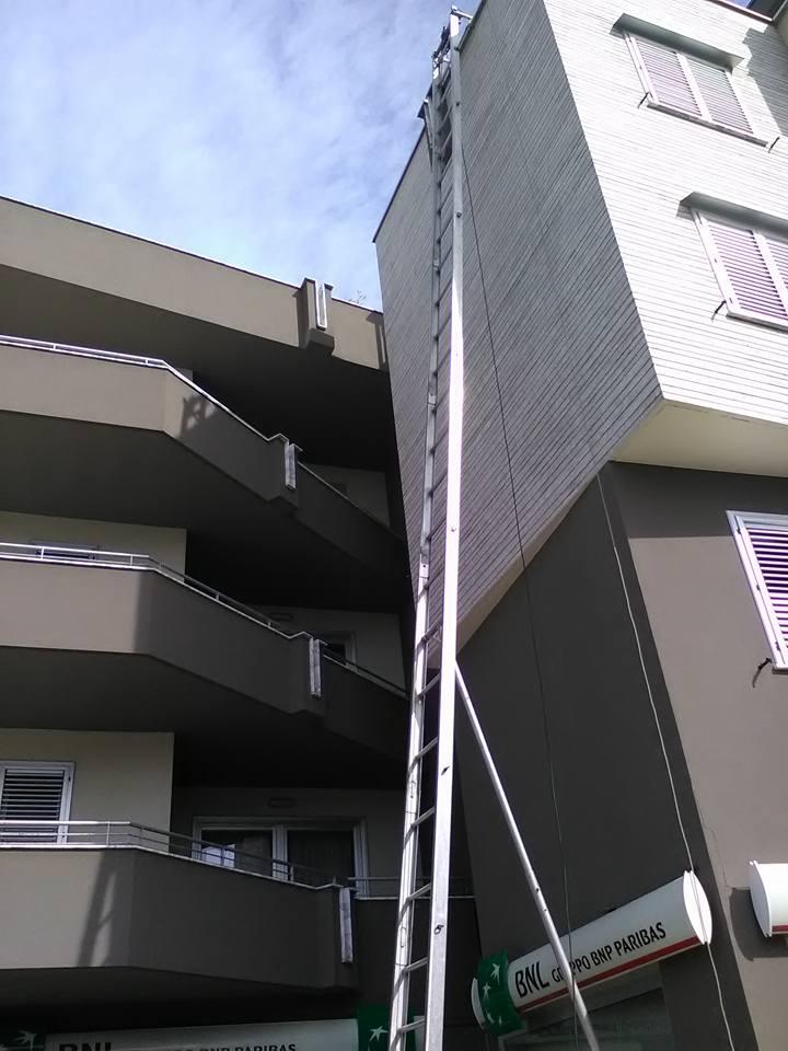 una lunga scala per traslochi vicino a un condominio