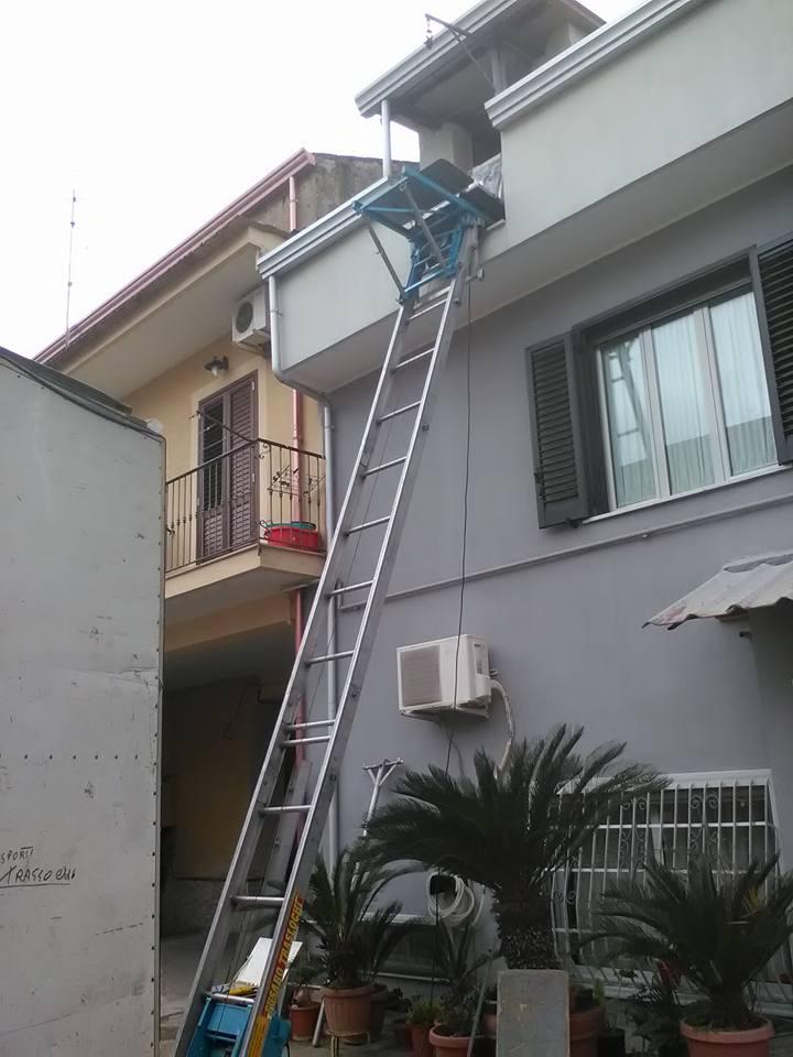 una scala per traslochi vicino a un condominio grigio