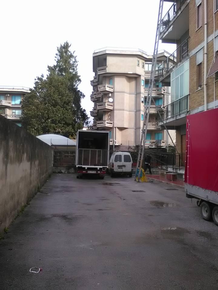 vista da lontano di un camion con il rimorchio aperto e una lunga scala