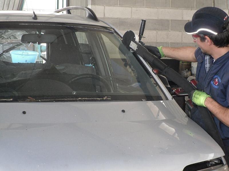 una mano che con un attrezzo con un disco da taglio stacca una portiera da una macchina