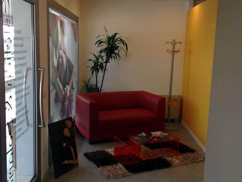 Comfortable sala d'attesa con tappeto di colori, un sofà rosso e piante