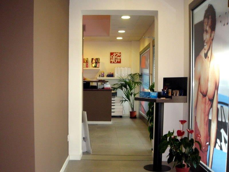 Corridoio di accesso alla ricezione dove vi è un poster di un giovane abbronzatura e una tavola alta con diversi prodotti