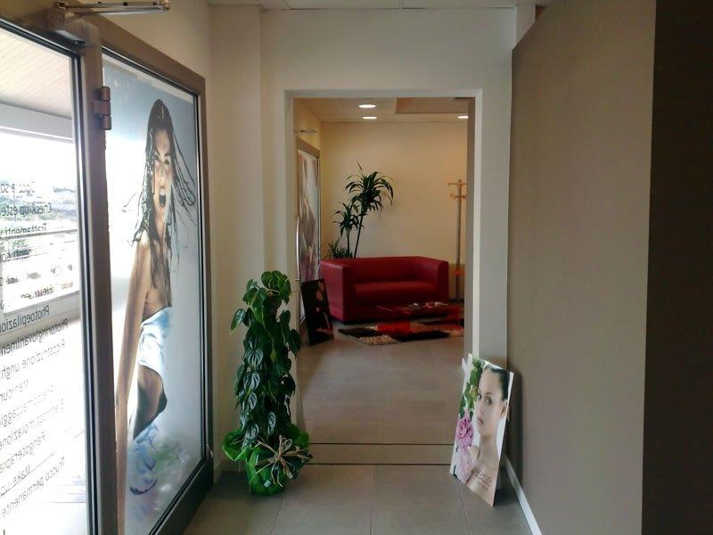 Corridoio di accesso alla sala d'attesa dove vi è un poster di una giovane bronceada e le piante danno un tocco naturale