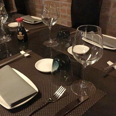 Vista parziale di una tavola preparata dove possiamo valutare tutti i dettagli: originali piatti ovalo rettangolari,tovaglioli in colore grigio perla,coperti di acciaio,bicchieri