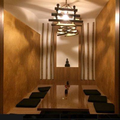 Mensa privato in toni bruni,stanghe di legno nella parete, tavola bassa di legno e i cuscini oscuri, un Buddha e luci soft lo completano