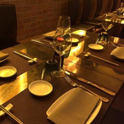 Tavola preparata: piatti, coperti, bicchieri, e le luci gialle diventano riflessi dorati