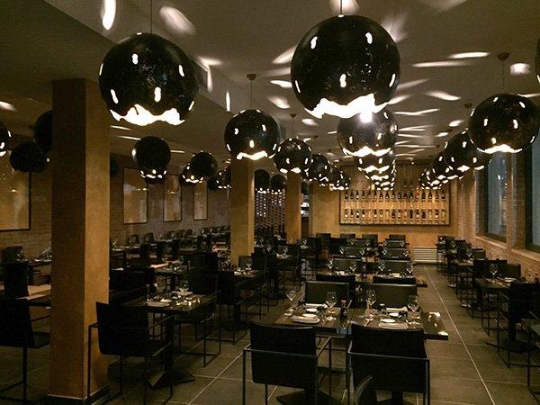 Vista generale del ristorante dove i toni bruni ,nero e acciaio si combinano