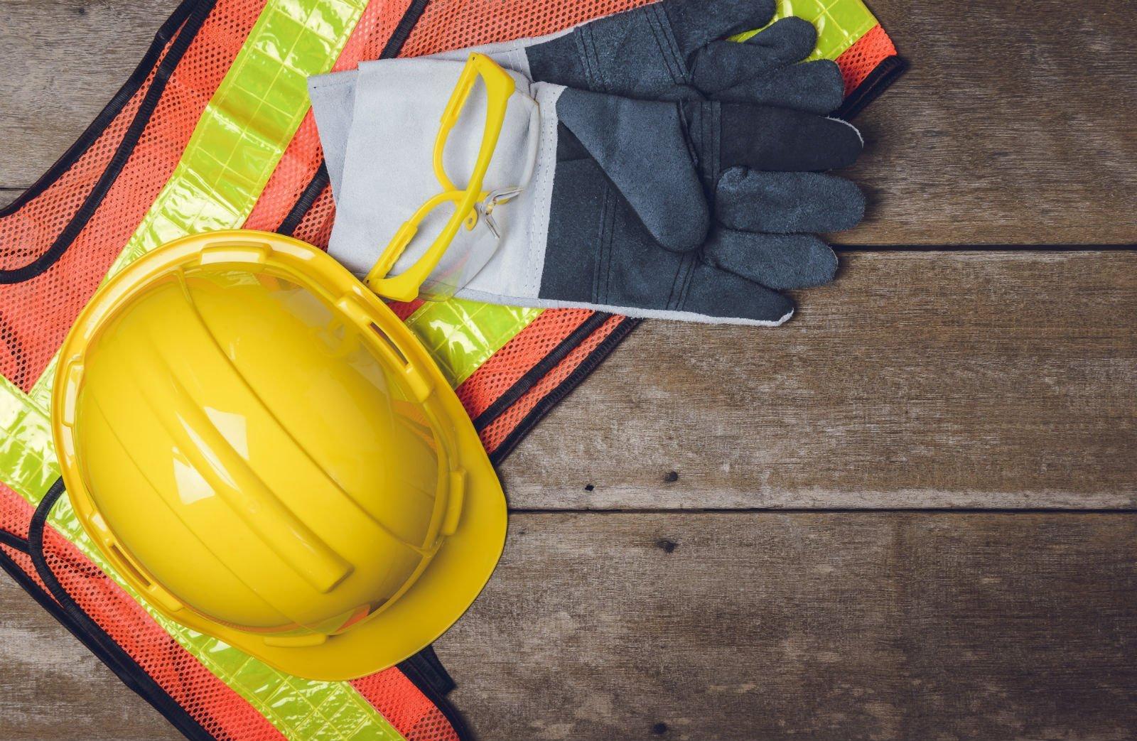 un casco antinfortunistico dei guanti e un giubbotto arancione