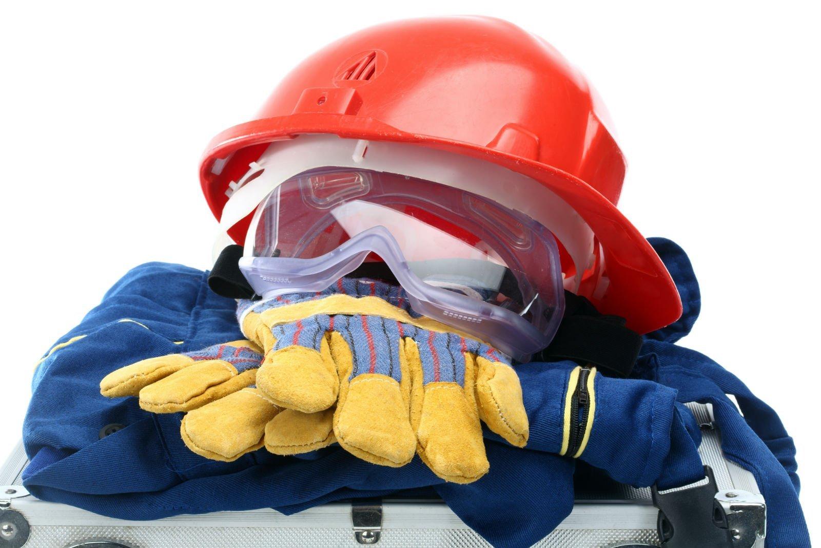 un casco antinfortunistico di color rosso, degli occhiali e dei guanti