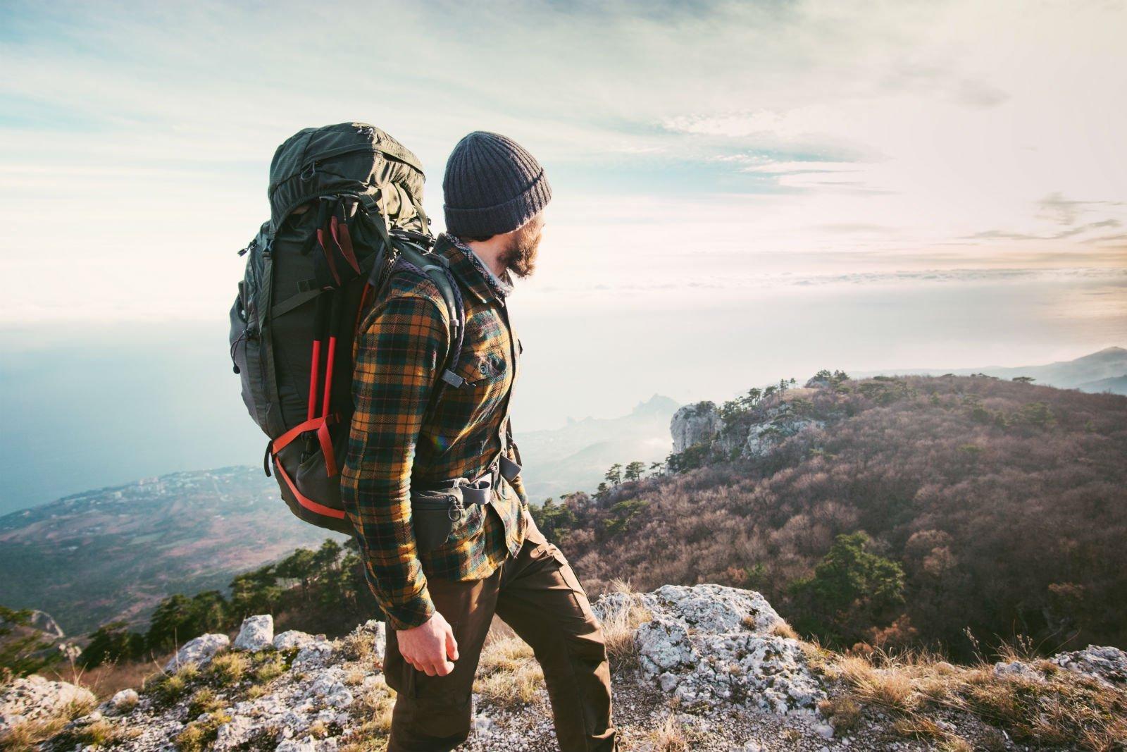 un ragazzo con uno zaino e un cappellino di lana in montagna
