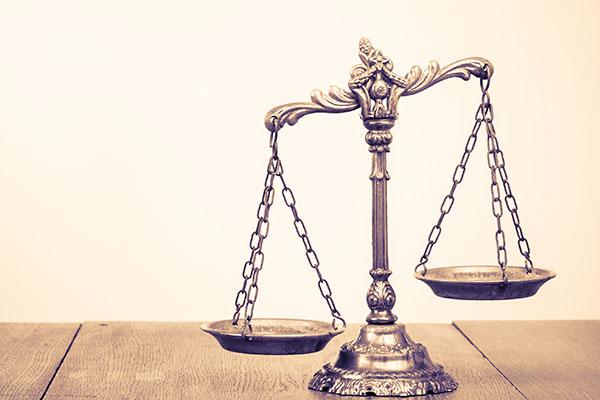 bilancia simbolo della legge su un tavolo di legno