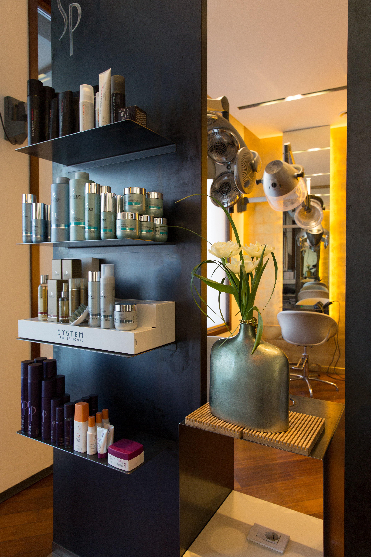 Esposizione di prodotti da parrucchiere con pianta ornamentale e specchio sulla destra