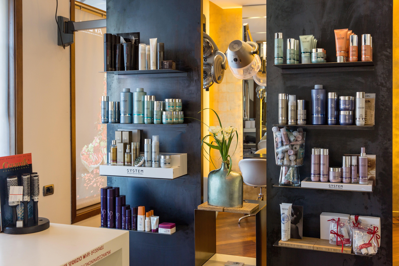 Due espositori scuri di prodotti per parrucchieri con specchio e pianta ornamentale al centro