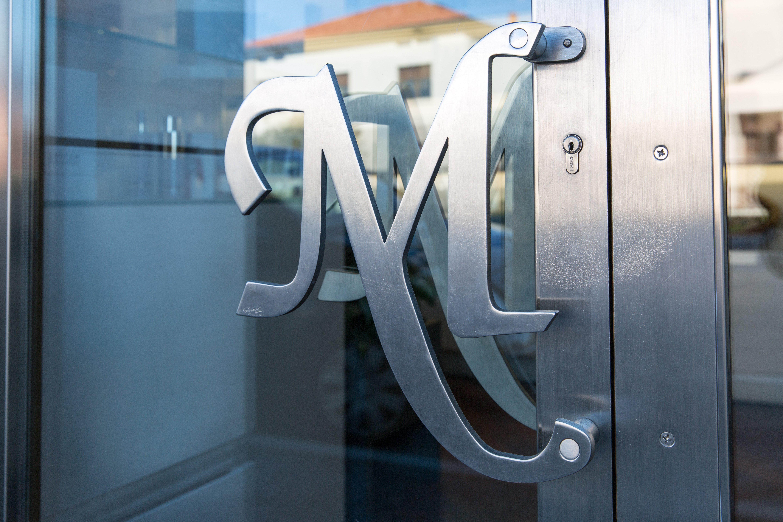 Battente a forma di M della porta d'ingresso del Salone Milena Parrucchiere a Pordenone