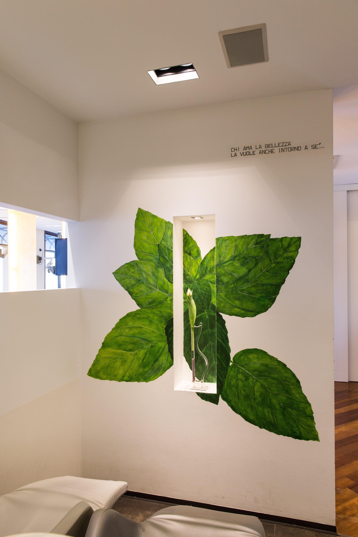 Decorazione di foglie verdi su muro bianco al Salone Milena Parrucchieri a Pordenone