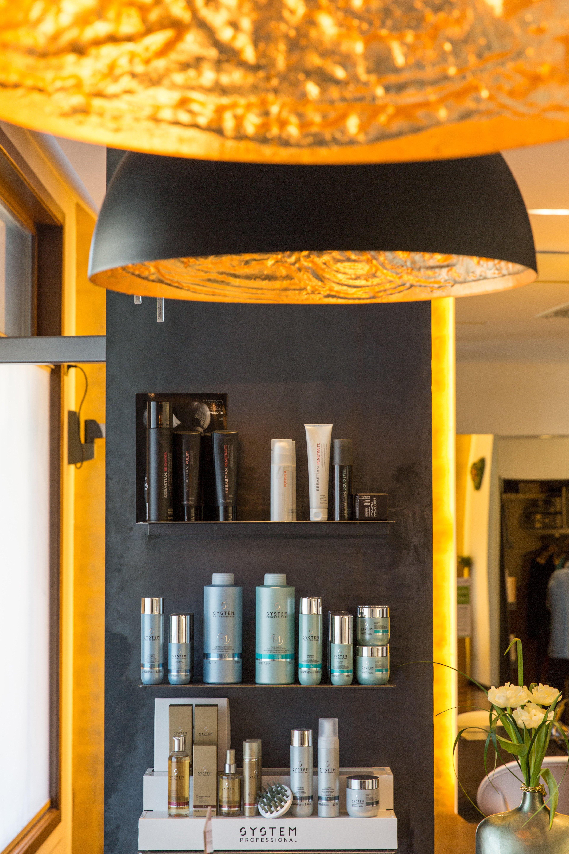 Esposizione di prodotti da parrucchiere su mobile nero con luci dorate