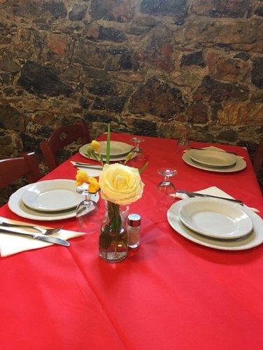 tavolo apparecchiato per quattro con rosa gialla centro tavola