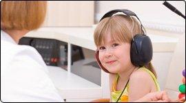 Bambina che prova uno strumento per l'udito