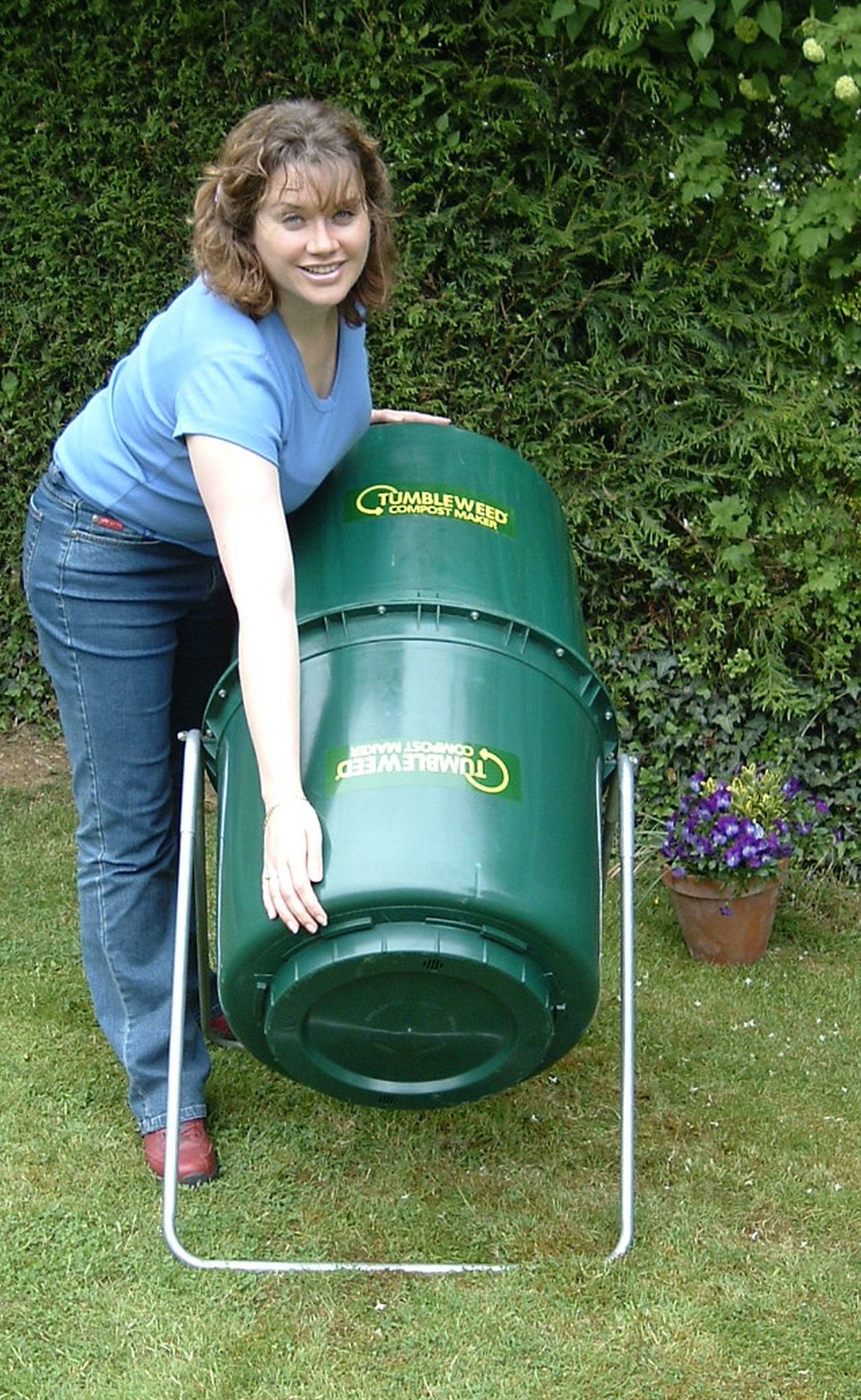 Woman rotating her Tumbleweed Compost bin in the garden