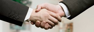 Two men in suits shaking hands on business start-up deal
