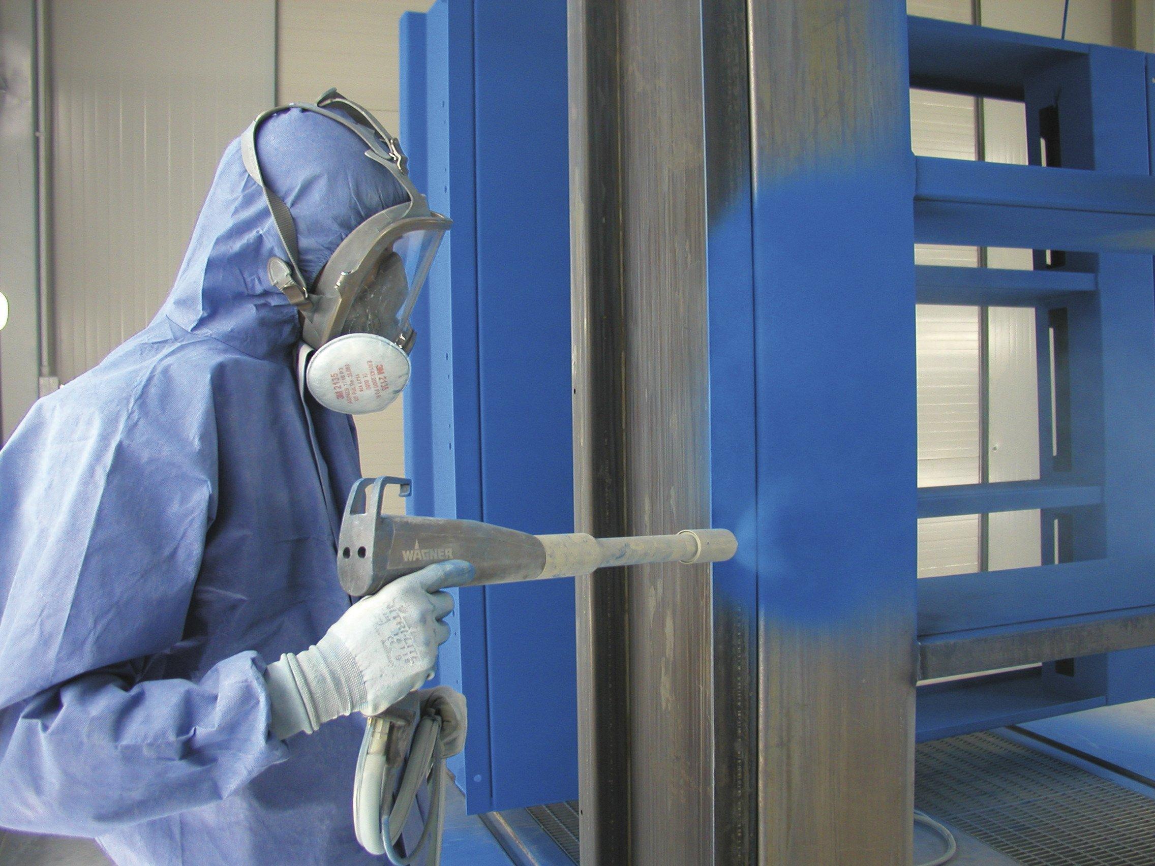operaio lavora con verniciatura a polvere