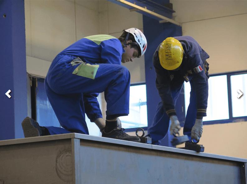 operai con casco mentre lavorano in impianto