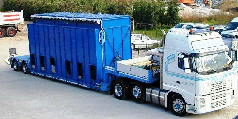 vista di un camion bianco con un rimorchio container azzurro