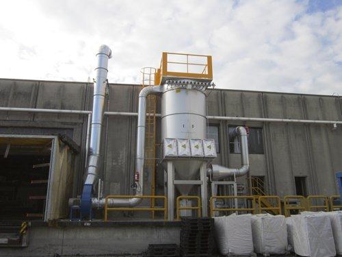 Un impianto grande in metallo collegato con delle tubature in acciaio accanto una industria