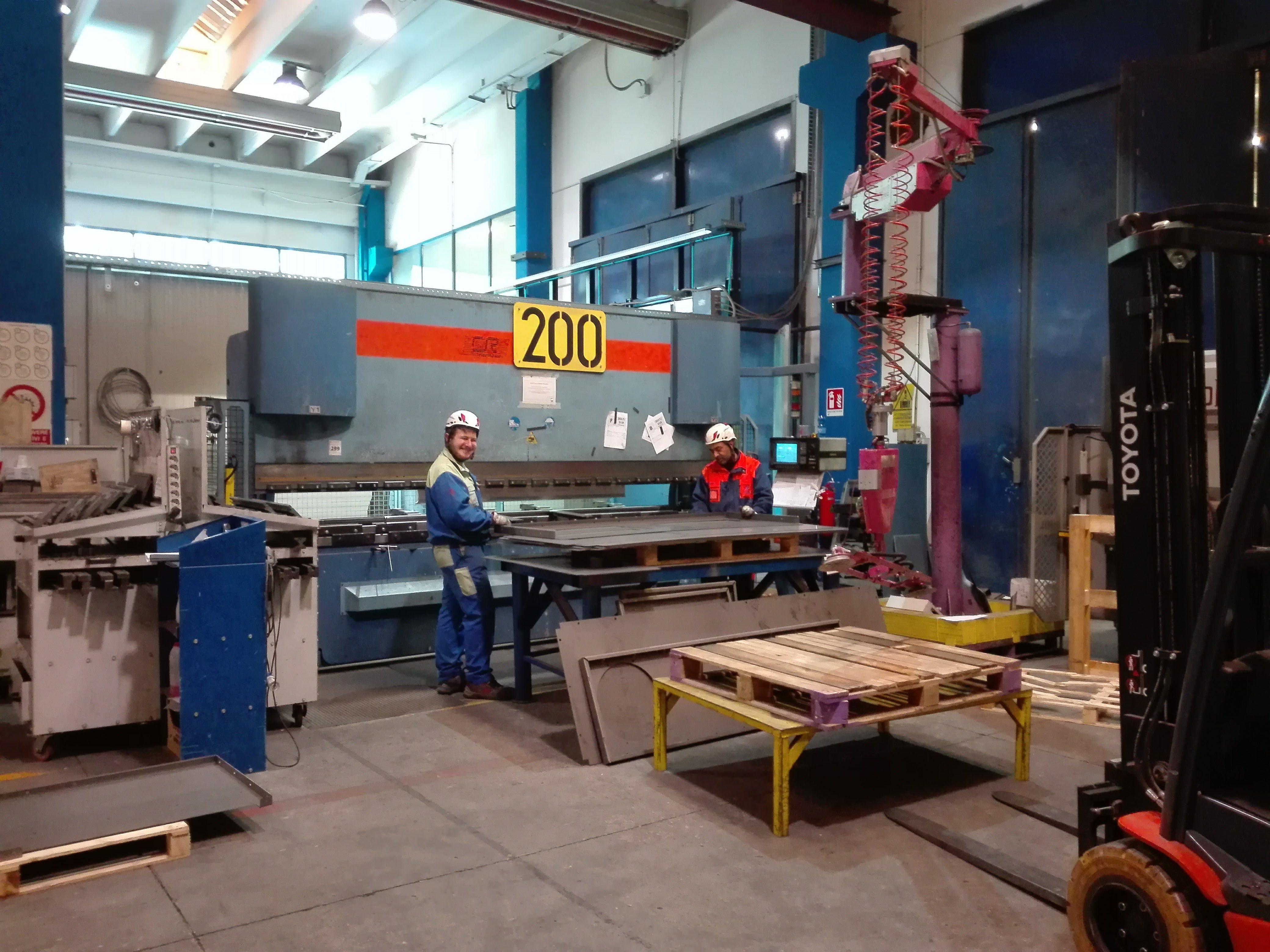 vista di una sala utensili sull'impianto con operai mentre lavorano