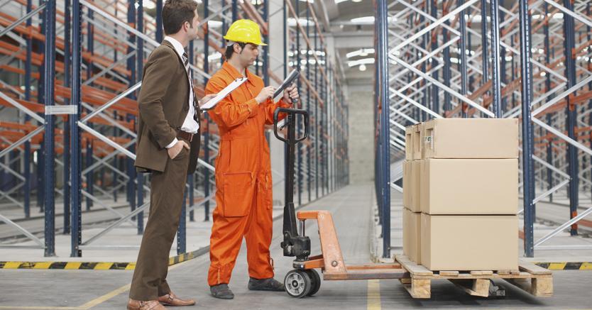 un tecnico e una persona in abito formale all`interno di un magazzino