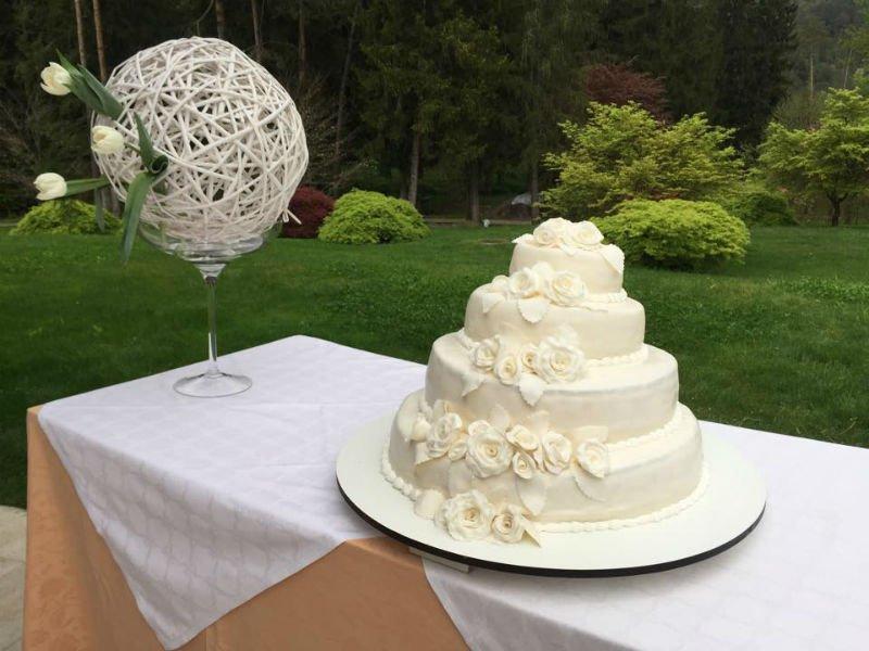 Torta di nozze di quattro piani di crema, sulla tavola anche una sfera di juta con tre tulipani bianchi
