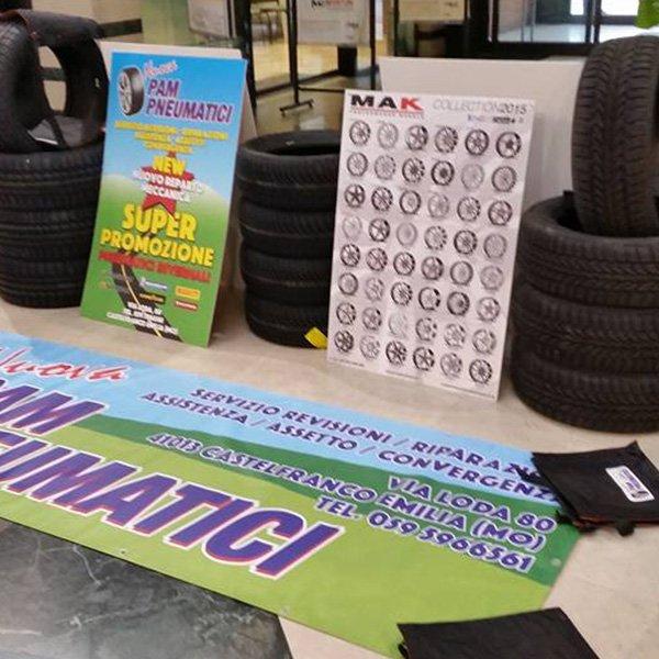 tre pile di pneumatici con cartellone con promozioni