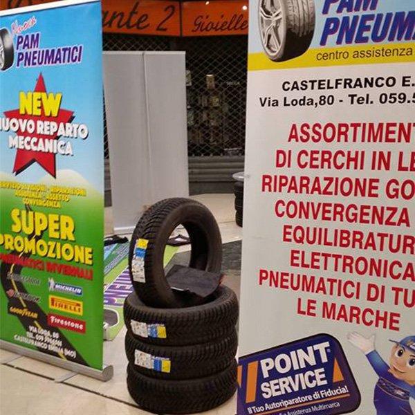 una pila di pneumatici con cartellone con servizi officina