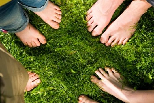family standing in a circle in the grass with bare feet