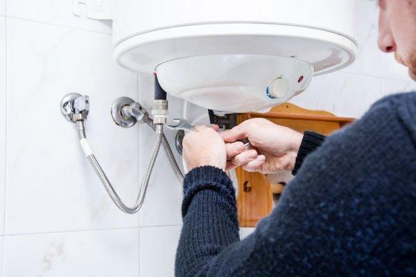 Operaio avvita le tubature di un boiler