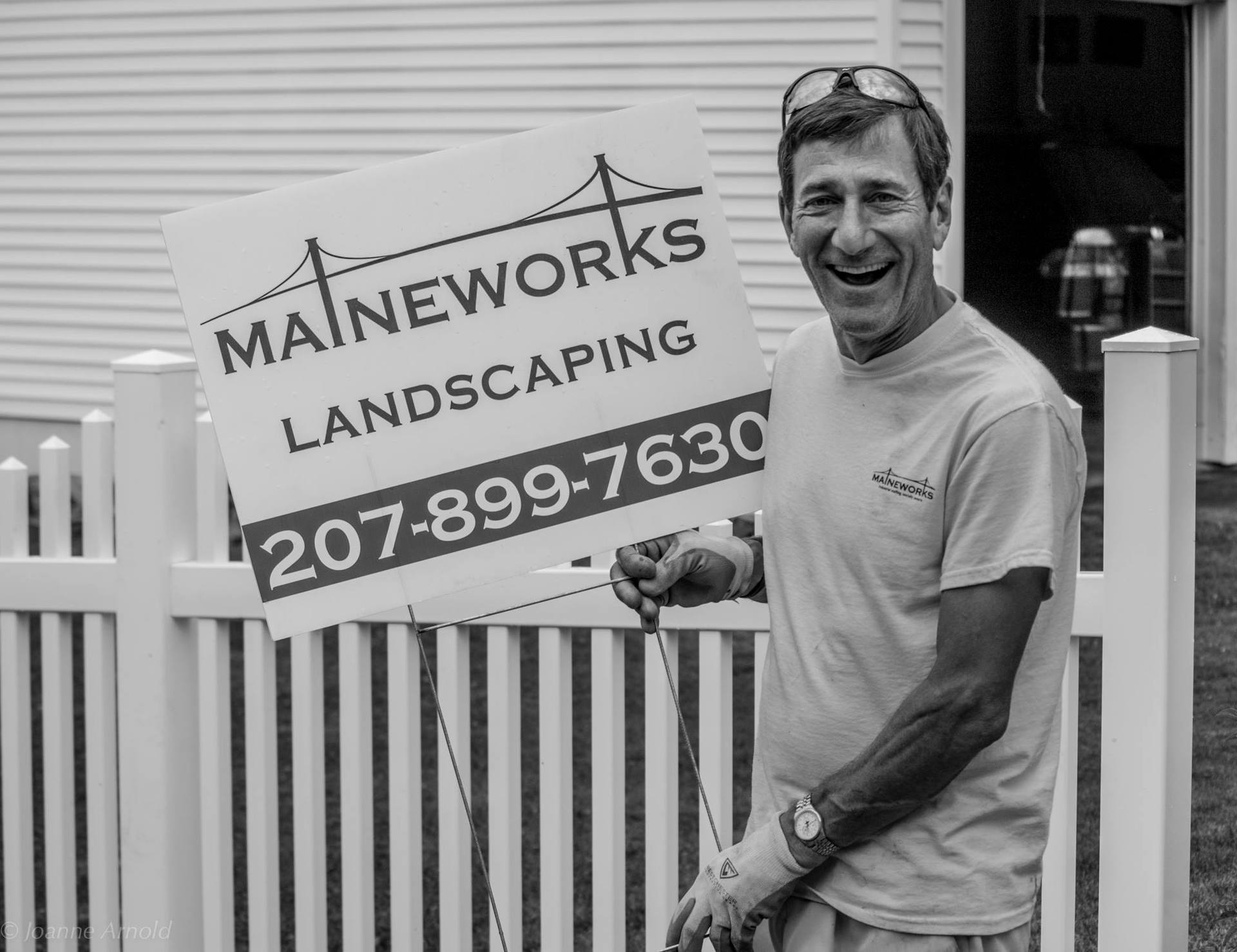 MaineWorks landscaping employee holding sign